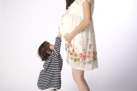 妊婦さんのお腹を触る子供