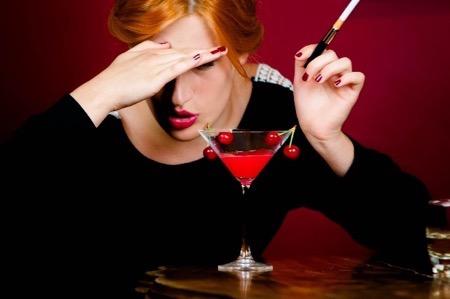 たばこを吸いながらお酒を飲む女性